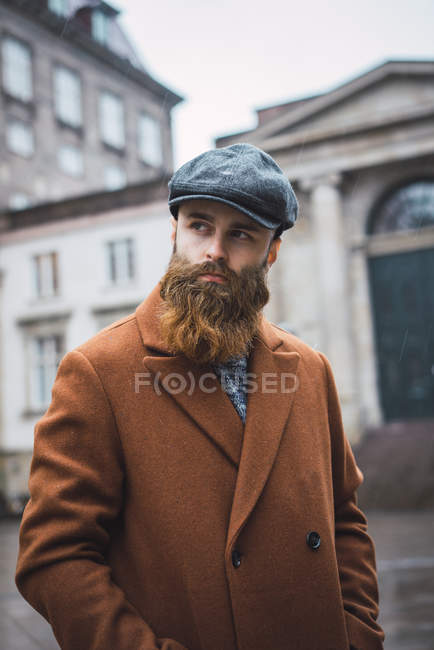 Portrait of bearded man wearing vintage coat and cap posing at square and looking away — Stock Photo