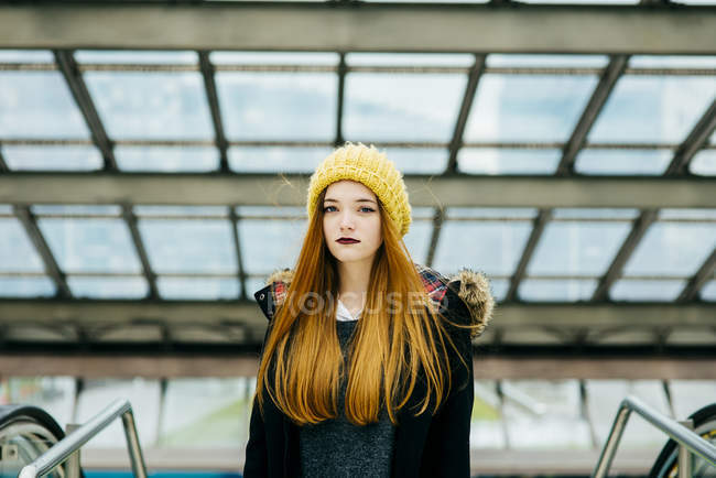 Young pretty woman in yellow knitted hat standing in mall and looking at camera — Stock Photo