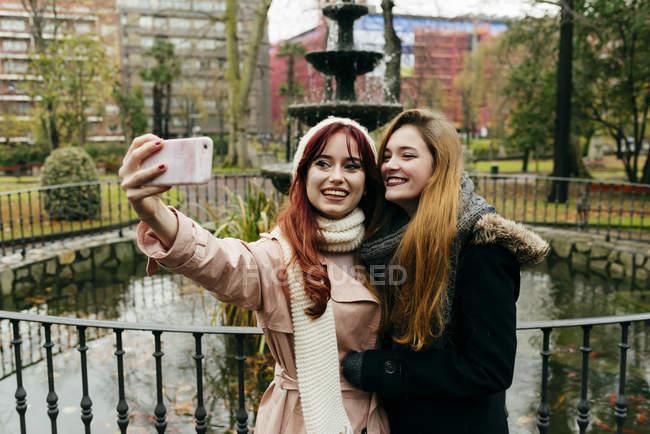 Zwei junge hübsche Freundinnen am Brunnen im Park stehen und nehmen selfie — Stockfoto