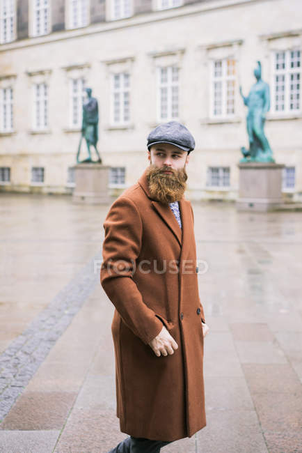 Side view of bearded man walking on street and looking over shoulder away — Stock Photo
