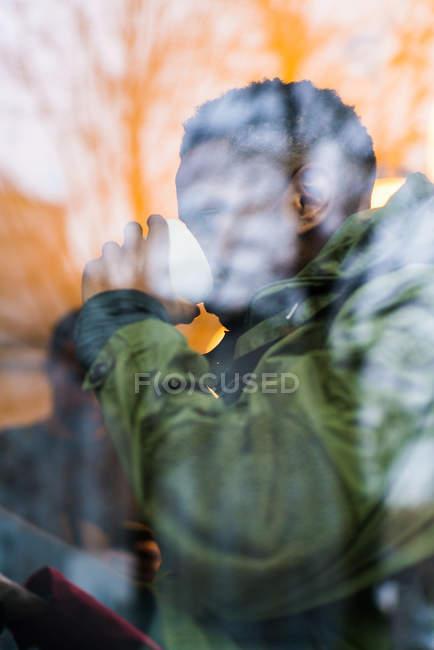 Vista attraverso la finestra per l'uomo in vestiti caldi bere caffè — Foto stock