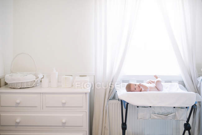 Infant child lying in bed in by window at home. — Stock Photo