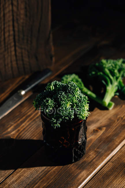 Close up view of fresh bimi broccoli bunch in glass on wooden table — Stock Photo