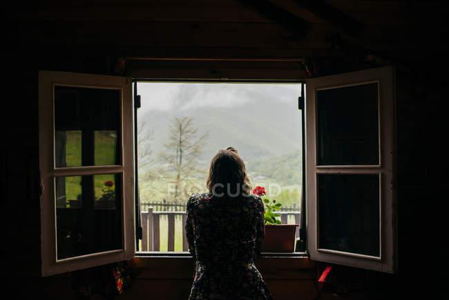 Rückansicht der Frau stützte sich auf die Fensterbank und Blick auf die Natur außerhalb. — Stockfoto