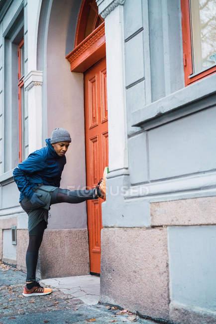Homme sportive échauffement et d'étirement des muscles de la jambe dans la scène de rue — Photo de stock