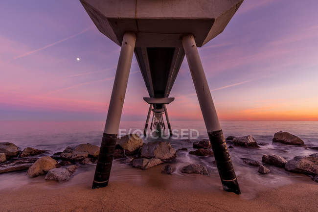 From below diminishing perspective shot of pier against sunset sky — Stock Photo
