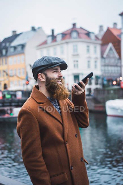 Seitenansicht der Mann in Mantel und Kappe mit Sprachsuche auf Smartphone am Fluss in der Stadt — Stockfoto