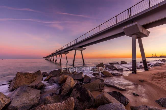 Diminishing perspective shot of pier against violet sunset sky — Stock Photo