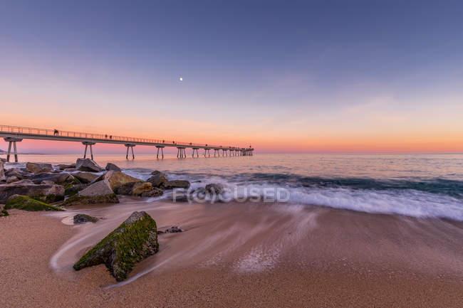 Coucher de soleil idyllique sur la plage avec jetée et vagues de surf — Photo de stock
