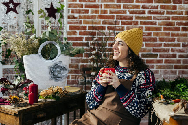 Portrait of smiling woman drinking hot beverage in floral atelier — Stock Photo