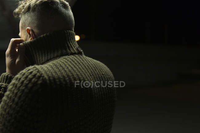 Rear view of stylish man in green sweater posing on parking lot — Stock Photo
