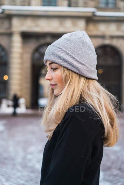 Боковой вид задумчивой блондинки, позирующей в зимнем городе — стоковое фото
