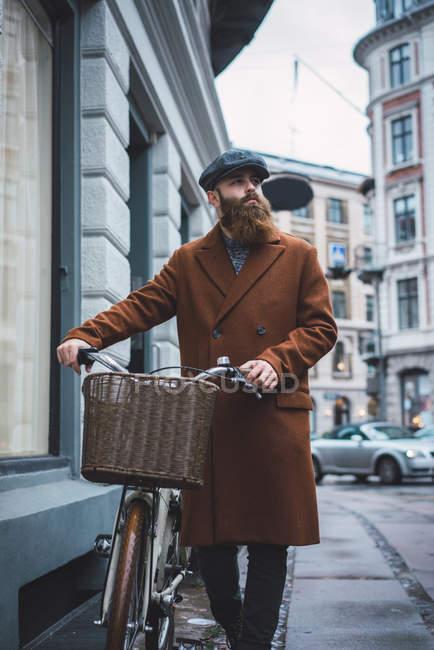 Vista frontal do homem respondendo boné e casaco andando com bicicleta vintage na cena da rua — Fotografia de Stock
