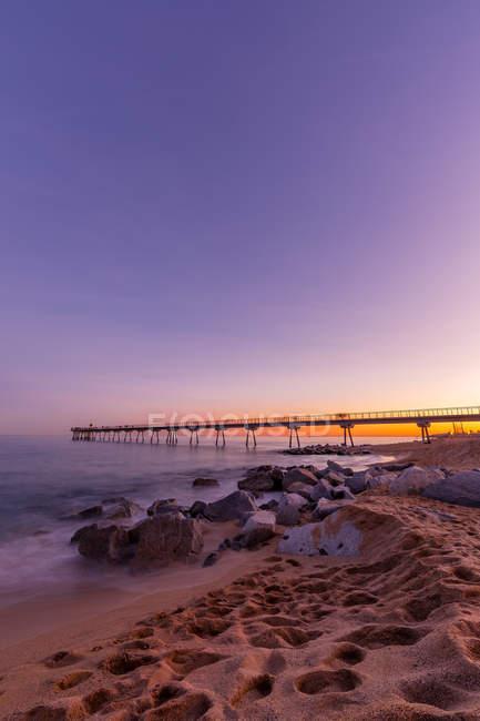 Idílica escena puesta de sol en la playa con muelle contra el cielo - foto de stock