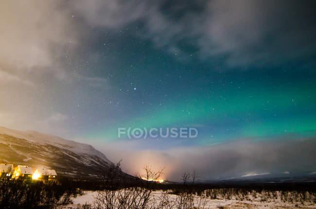 Vue panoramique du petit village de prairie d'hiver sur les aurores boréales dans le ciel sur fond — Photo de stock