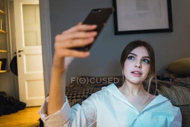 Porträt der Frau, die Selfie mit Smartphone im Stock zu Hause — Stockfoto