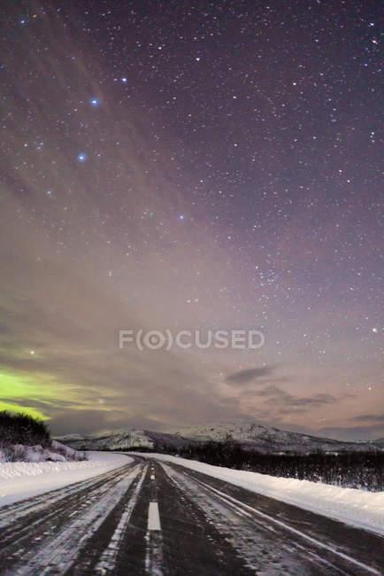 Точки зору асфальтована дорога покриті снігом під зоряним небом з Північним сяйвом — стокове фото