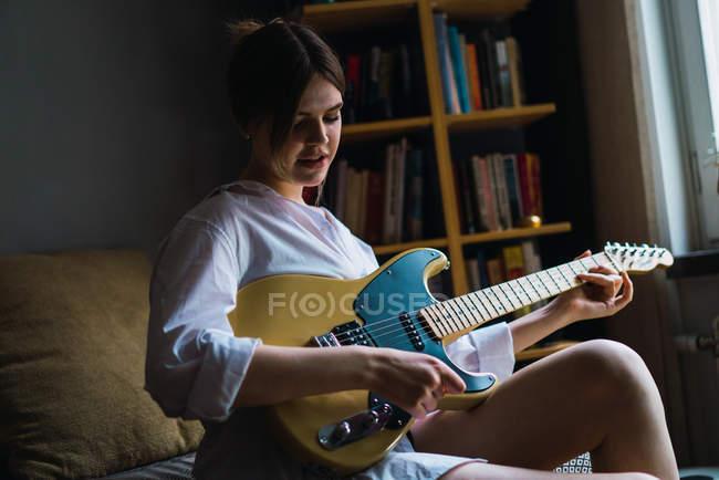 Porträt einer jungen Frau, die mit Gitarre auf dem Bett posiert — Stockfoto