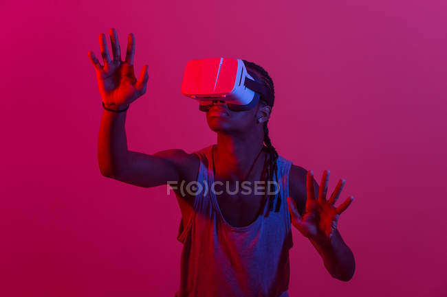 Portrait of young man using VR headset in red lit room — Stock Photo