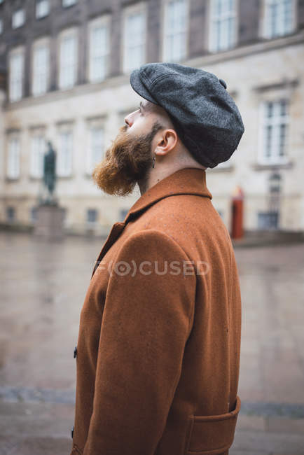 Side view of bearded man in posing in coat and cap and looking up — Stock Photo