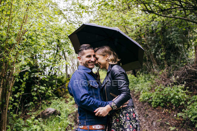 Happy couple embracing while standing under umbrella in green forest. — Stock Photo