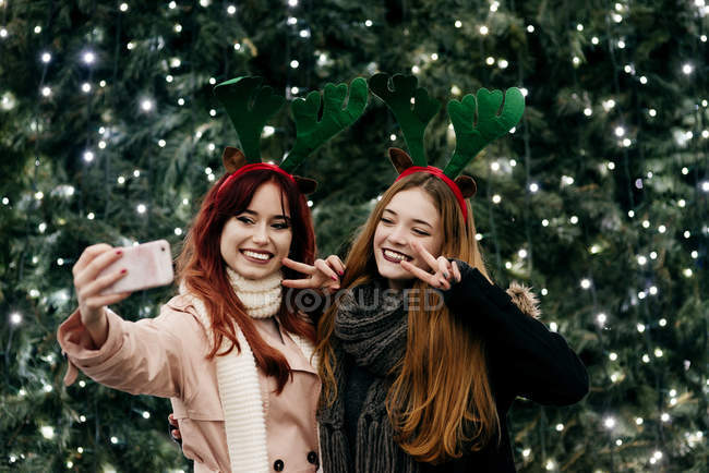 Smiling women taking selfie on smartphone at illuminated Christmas tree — Stock Photo