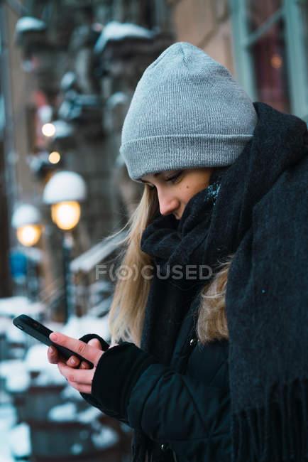 Vue latérale du jeune blondeoman à l'aide d'un smartphone sur la rue d'hiver — Photo de stock