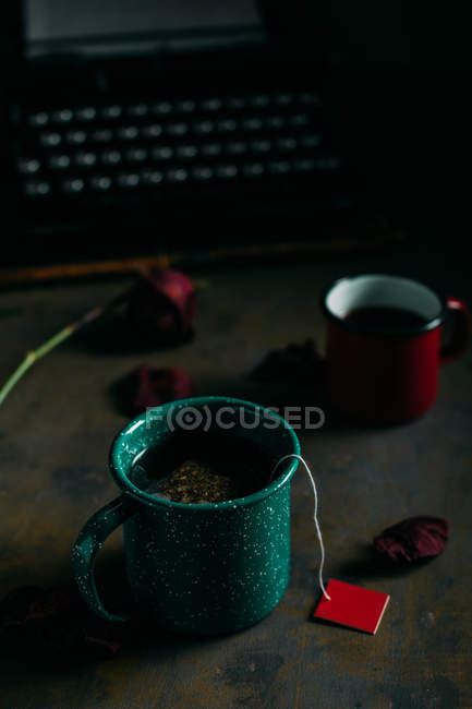 Close up view of ups of coffee and tea at table with dried rose and retro typewriter — Stock Photo