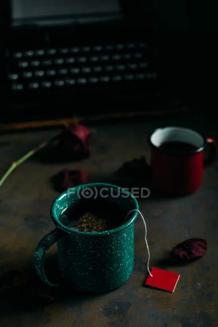Крупним планом подання ups кави і чаю за столом з сушені троянди і ретро машинці — стокове фото
