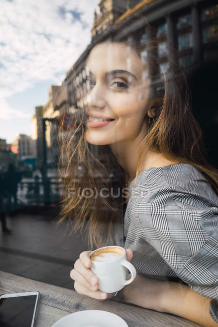 View through window of smiling woman with coffee cup looking at camera — Stock Photo