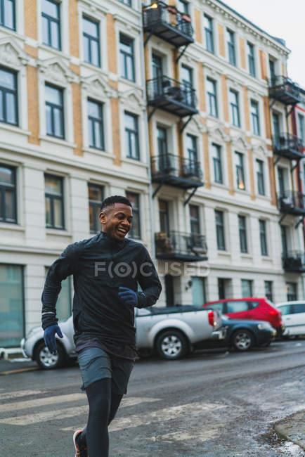 Спортивный человек в теплых спортивной, работающие на улице — стоковое фото