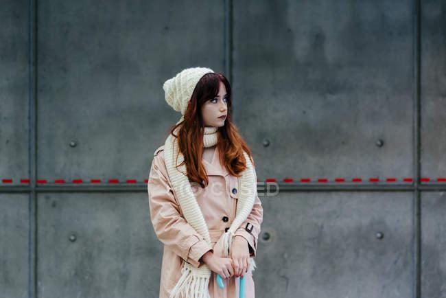 Donna pensierosa in piedi contro il muro preoccupazione e guardando altrove — Foto stock