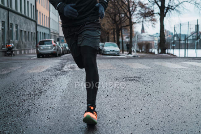 Crop male running on winter street — Stock Photo