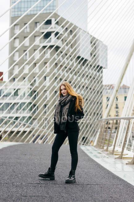 Elegante giovane donna in posa sul ponte urbano . — Foto stock