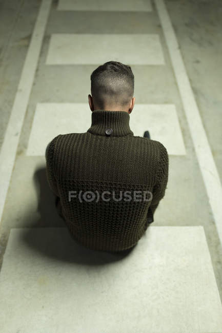 Rear view of man sitting on concrete floor — Stock Photo