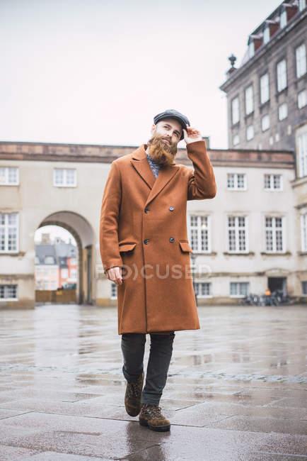 Ritratto di uomo barbuto alla moda gesticolare con cappuccio sulla scena della strada — Foto stock