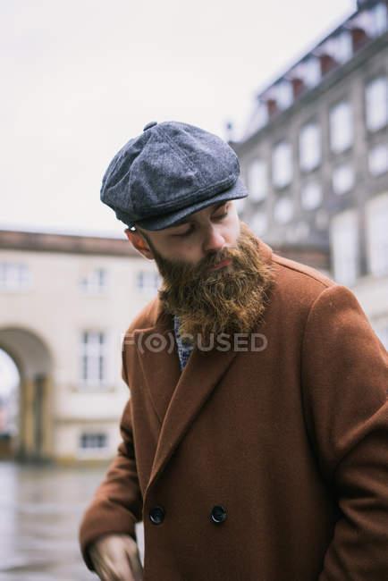 Uomo barbuto elegante posa con cappello e cappotto vintage e guardando  sopra la spalla di distanza 26fb9cb60713