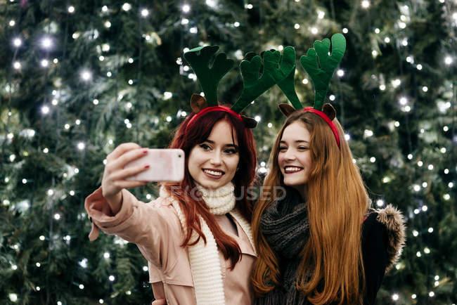 Fröhliche hübsche Frauen, die die Selfie mit Smartphone bei festlichen Weihnachtsbaum auf Straße — Stockfoto
