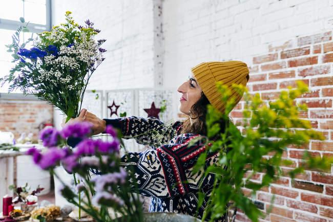 Seitenansicht einer Frau, die Blumen im Blumenatelier arrangiert — Stockfoto