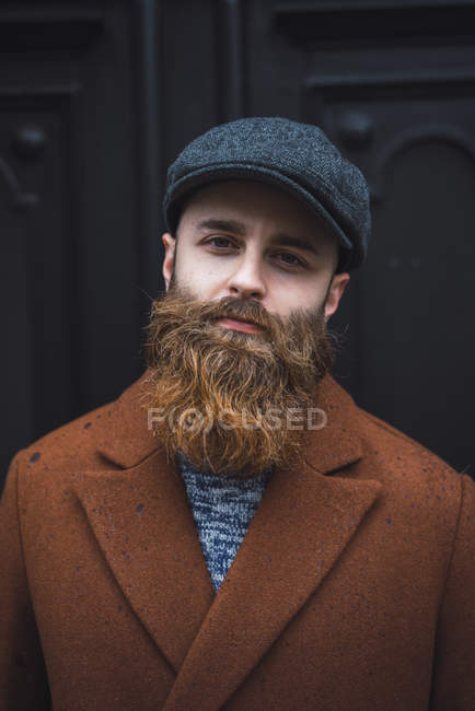 Portrait of bearded man wearing brown coat and cap looking at camera — Stock Photo