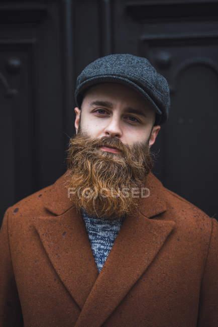 Retrato de homem barbudo vestindo casaco marrom e boné olhando para a câmera — Fotografia de Stock