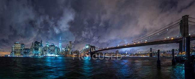 Vue sur le paysage urbain vers un grand pont et des tours de ville éclairées la nuit . — Photo de stock