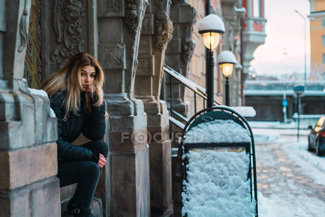 Portrait of bored blonde woman sitting on facade at winter street and looking at camera — Stock Photo