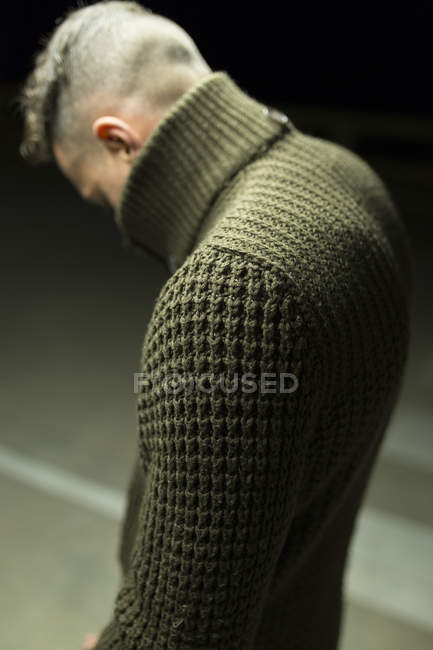 Side view of stylish man standing on parking lot and looking down — Stock Photo