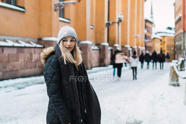 Stylish blonde girl posing on snowy street — Stock Photo