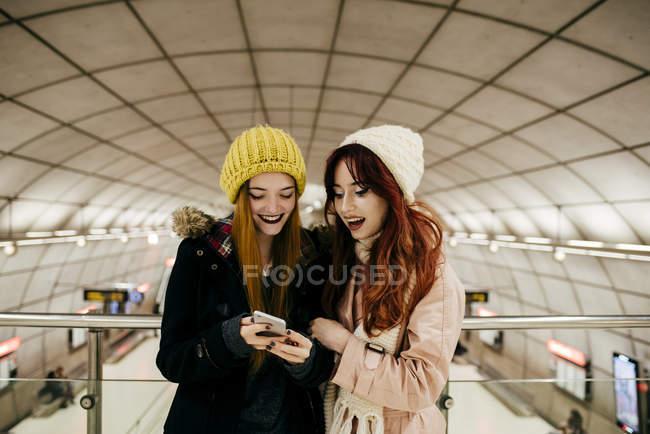 Portrait de deux femmes gaies utilisant le téléphone — Photo de stock