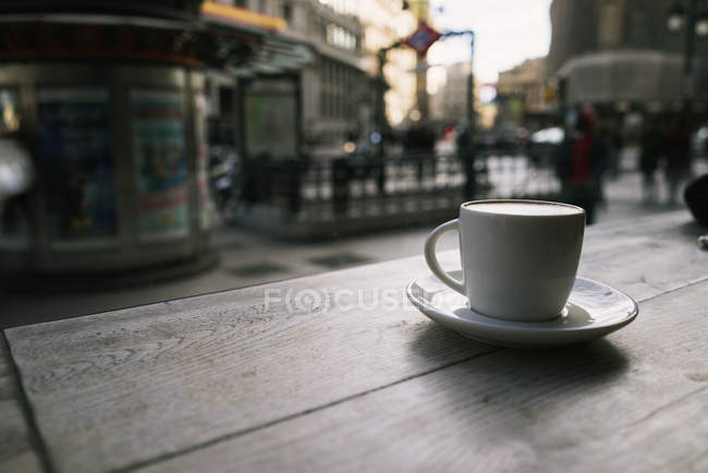 Close up view of fresh coffee placed on wooden table in urban cafe. — Stock Photo