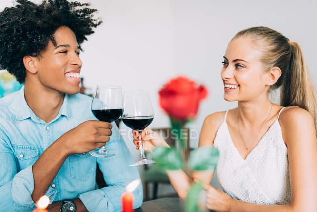 Portrait of smiling interracial couple clinking glasses at romantic dinner on valentines day at home — Stock Photo