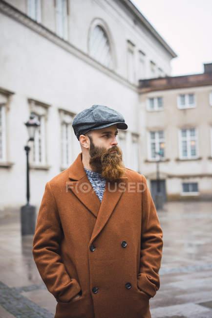 Retrato de un hombre barbudo con abrigo y gorra caminando por la ciudad y mirando hacia otro lado - foto de stock