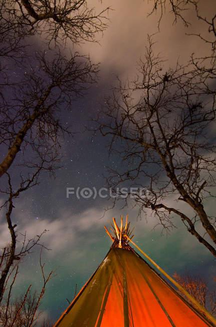 Erntezelt mit Lagerfeuer im Wald in der Winternacht mit Polarlicht — Stockfoto